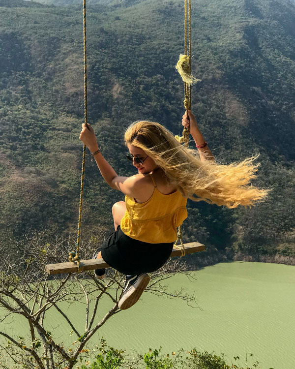 Alana on a swing above a river