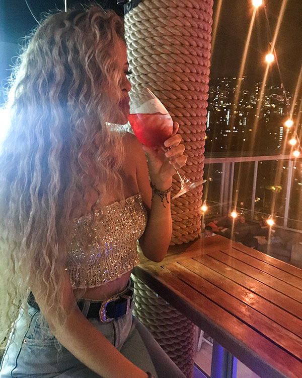 Alana drinking a cocktail