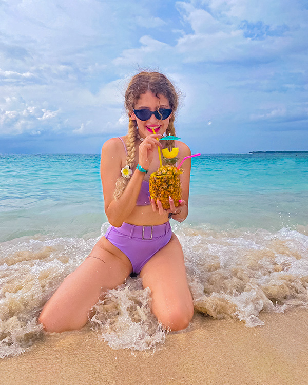 Alana kneeling in the surf holding a cocktail